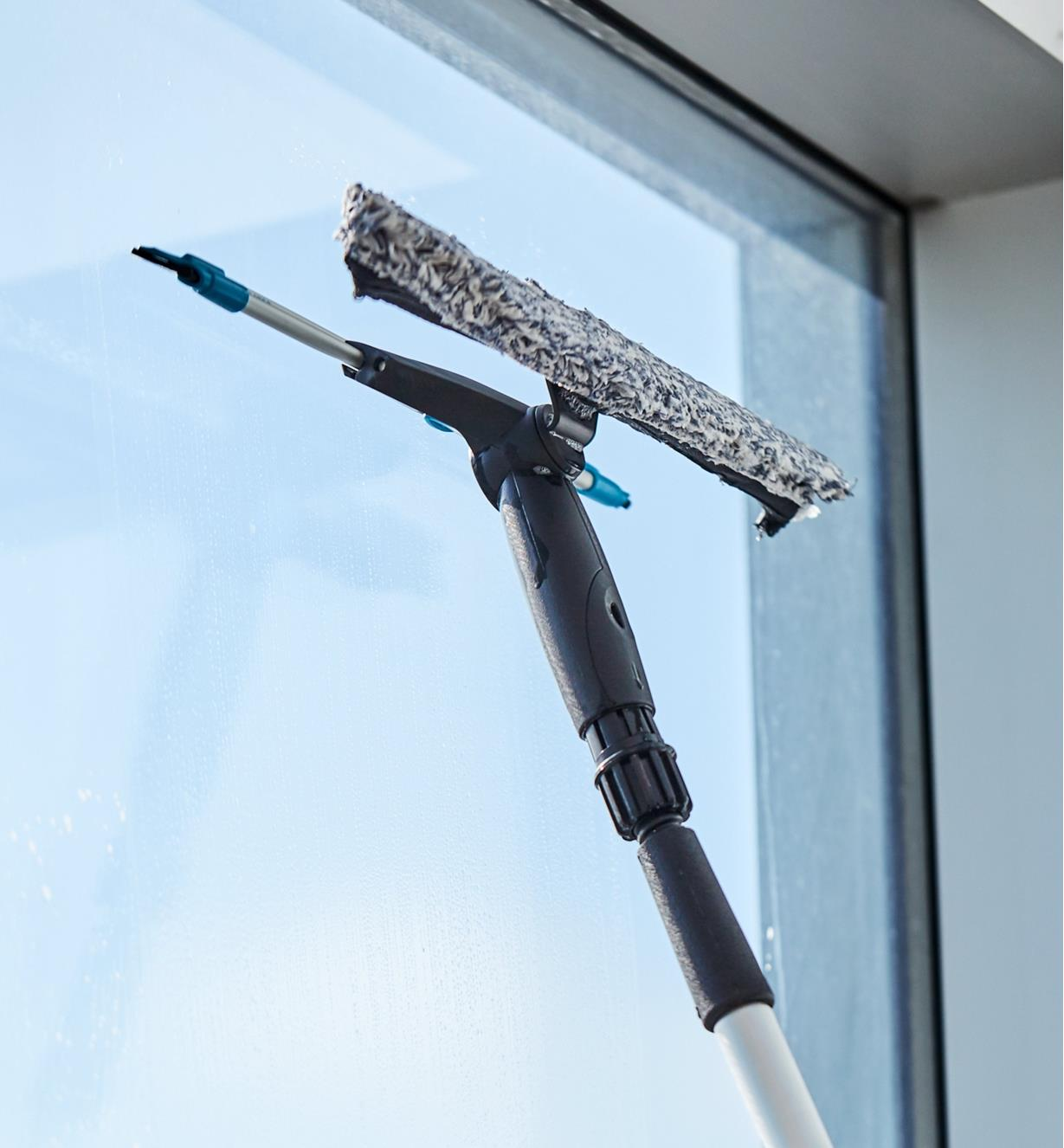 Using the rubber squeegee to wipe a window dry