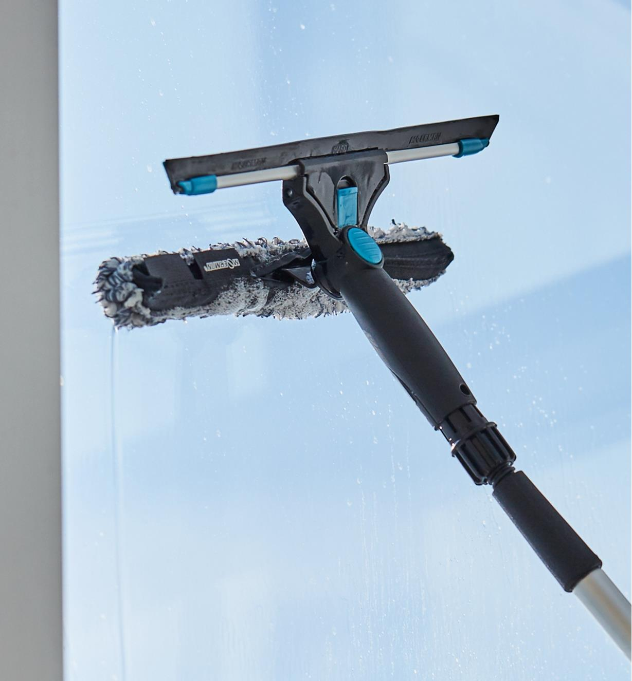 Using the microfiber scrubber of the dual-head window-washing set to clean a window
