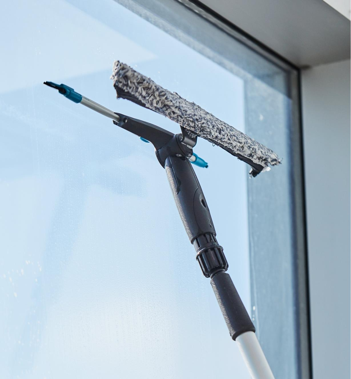 Using the rubber squeegee of the dual-head window-washing set to wipe a window dry