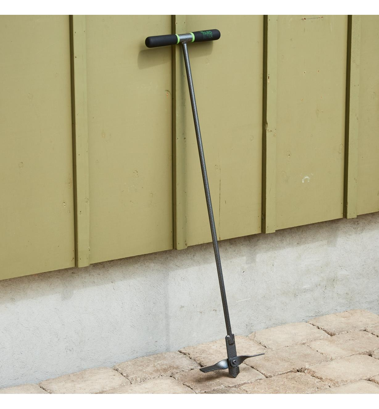 A compost aerating tool leaning against a wall
