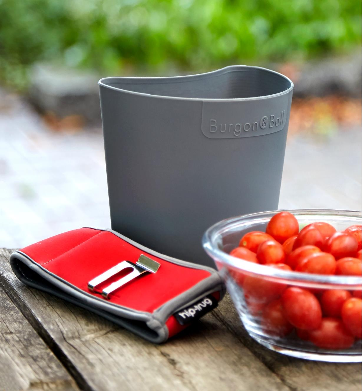 A small hip-trug removed from its neoprene holster, next to a small harvest of grape tomatoes