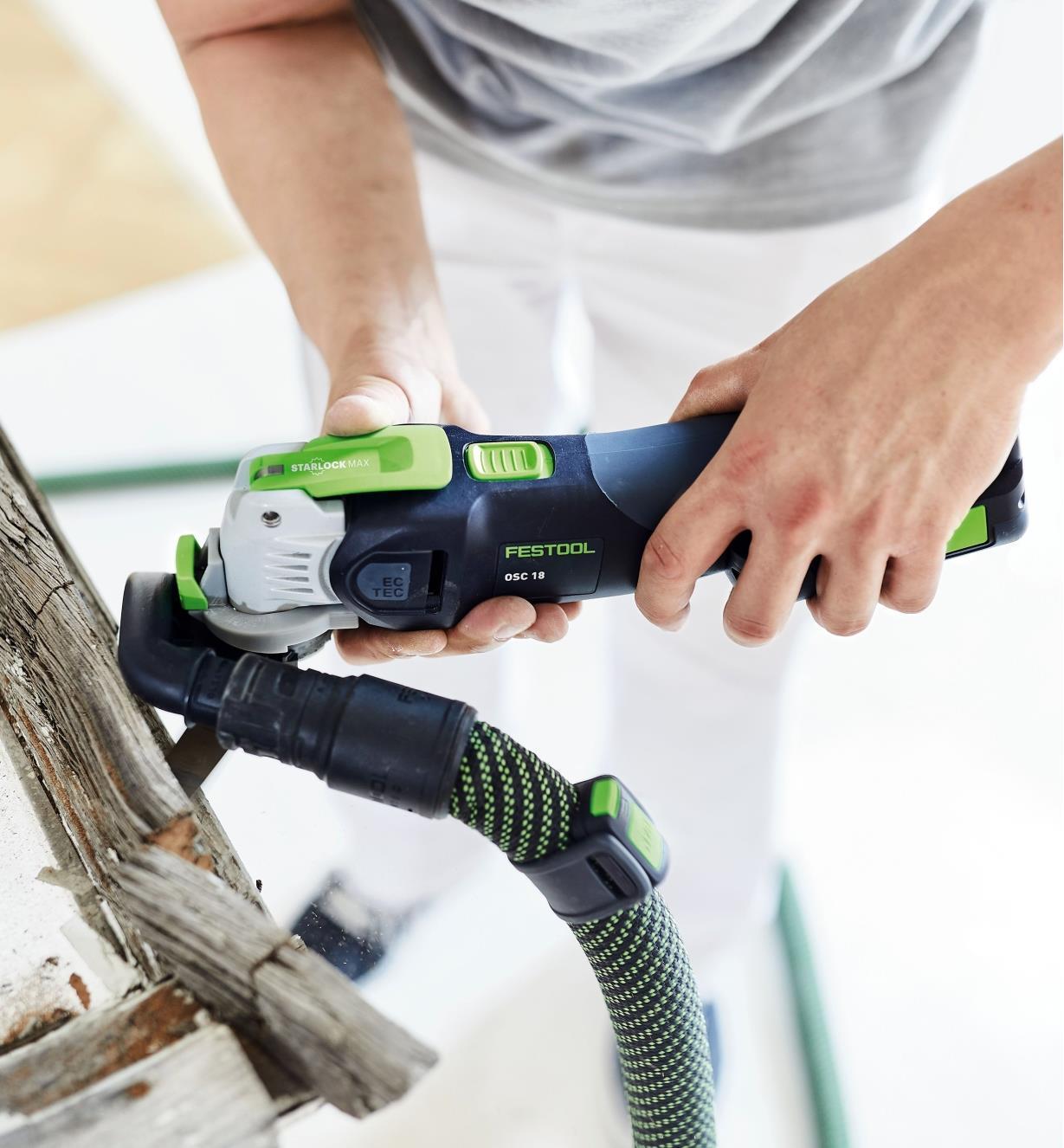 Personne utilisant un outil oscillant Vecturo OSC 18 muni d'une lame segmentée pour enlever le cadre en bois d'une fenêtre